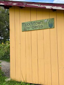 Yellow building with green sign that says Moodytown Gardens with drawing of plant