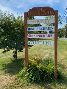 Lions Farm sign - honey, blueberries, raspberries, and zucchini, with orange flowers below