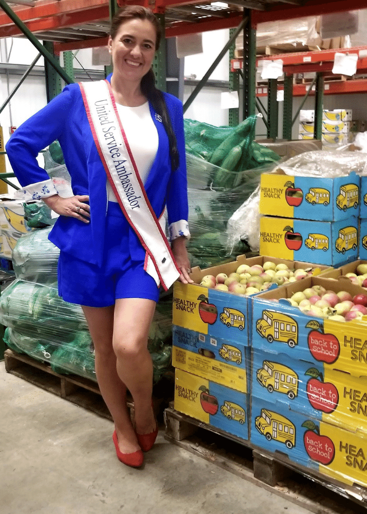 Misty Coolidge, United Service Ambassador for Worldwide USA Pageants in Good Shepherd Food Bank's Auburn distribution center. She's standing in front of produce in a blue suit and wearing her sash.
